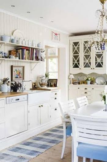 A cute white Swedish kitchen with a worn flat-weave rug.