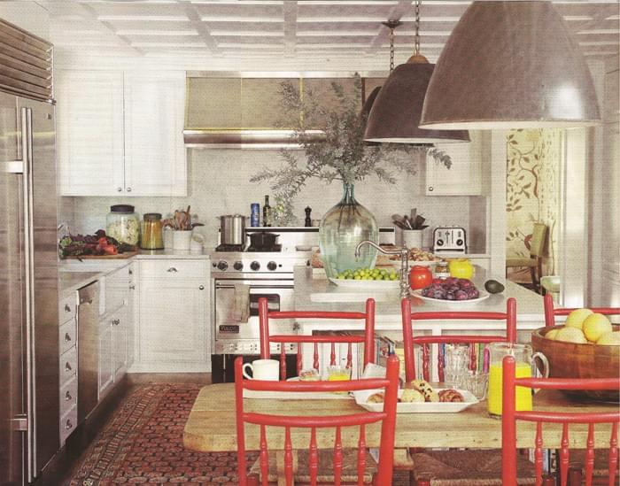 A 19th Century Caucasian runner and red chairs add a splash of color in the kitchen
