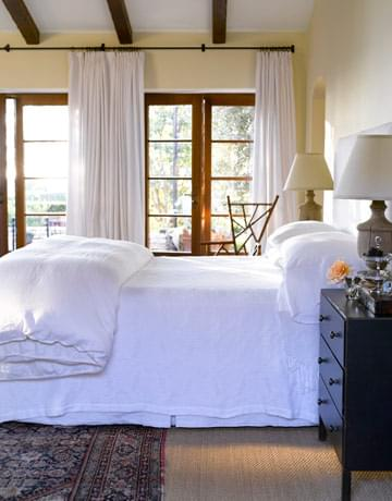 Design duo Dana Abbott and Kim Fiscus layer in a bedroom. Again the rug is the only pattern in the room.